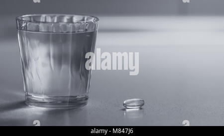 Vitamin capsule with a glass of water on the table - Stock Photo