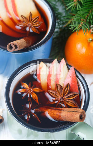 Mulled wine with Apple, citrus, cinnamon, cardamom and star anise on wooden background. Traditional hot Christmas - Stock Photo