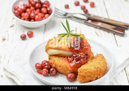 Baked breaded Camembert cheese (brie) with fresh berries and cranberry sauce with rosemary on a white background. - Stock Photo