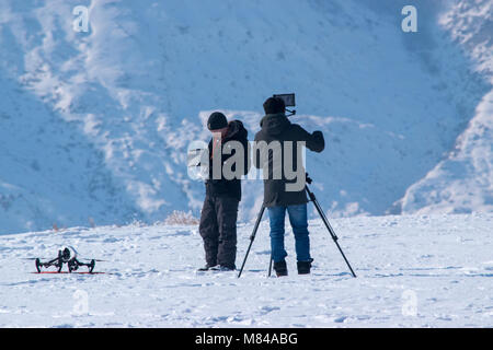 A camera man films a drone operator preparing to launch near Horsethief Canyon north of Drumheller, Alberta. Operating - Stock Photo
