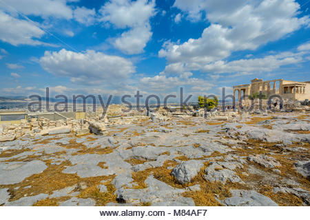 A warm summer day in Athens Greece as tourists enjoy the city view and explore the ancient Erechtheion on Acropolis - Stock Photo