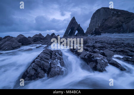 Dramatic coastal scenery with Blackchurch Rock at Mouthmill Cove on the North Devon coast, England. Winter (February) - Stock Photo