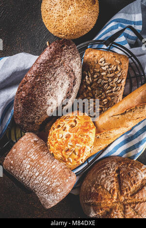 Variety of fresh homemade grain bread, in a metal basket, dark rusty background copy space top view - Stock Photo