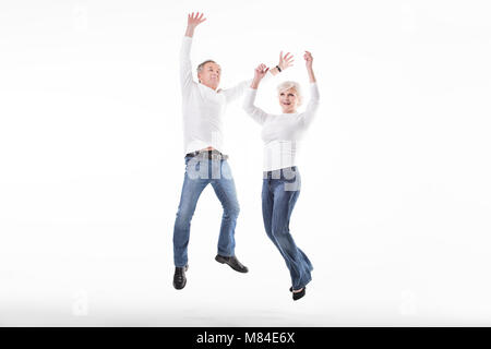 Happy mature couple jumping in studio, smiling. - Stock Photo