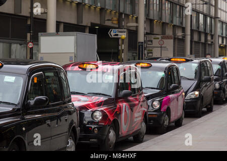 Parked London black cab taxis awaiting a fare near Kings Cross Station with taxi light illuminated. - Stock Photo