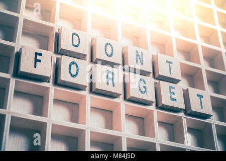 Macro Of A Don't Forget Reminder Formed By Wooden Blocks In A Typecase - Stock Photo