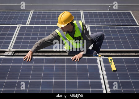 Male worker working on solar panels at solar station - Stock Photo