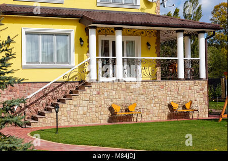 Exterior of luxury home with terrace, green yard and beautiful iron benches - Stock Photo