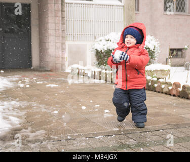Baby boy while it snows runs with a snowball in his hands - Stock Photo