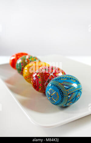 Colorful handmade easter eggs in row on white plate. Traditional czech decoration. - Stock Photo