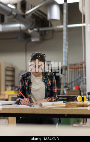 Female carpenter working at workshop - Stock Photo