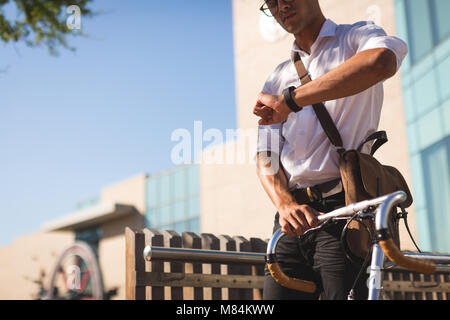 Businessman checking time while walking with his bicycle - Stock Photo