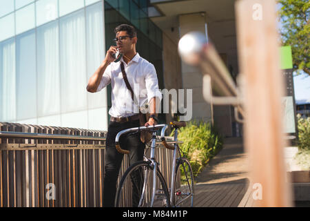 Businessman talking on mobile phone while walking with his bicycle - Stock Photo