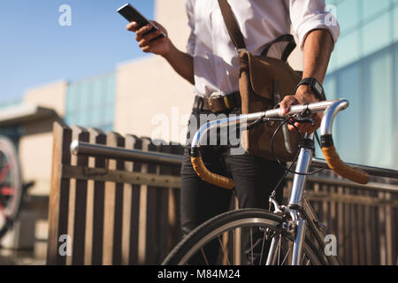 Businessman using mobile phone while walking with his bicycle - Stock Photo