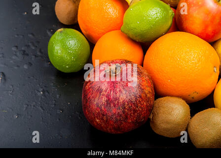 Variety of fresh fruits on dark background from slices of kiwi, bananas, aplle and orange ,copy space - Stock Photo