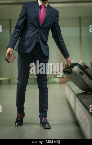 Businessman taking their baggage from baggage carousel - Stock Photo