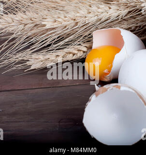baking background with bake ingredients,  ears, egg, Yolk, shell, flour and butter on rustic wooden, top view, banner - Stock Photo