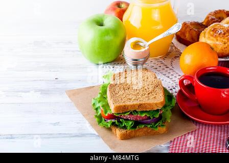 Breakfast stile. Homemade sandwich  with bacon, tomato, lettuce, glass juice, coffee, egg,  on breakfast on white - Stock Photo