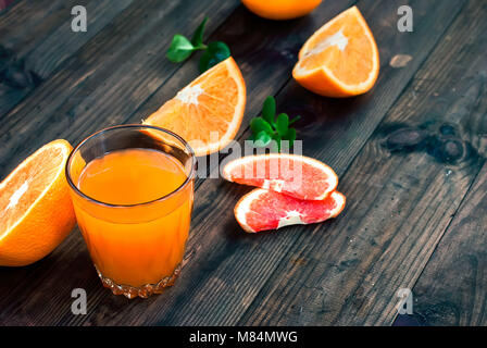 glass of fresh orange juice, whole orange and orange slices group on a dark wooden table - Stock Photo