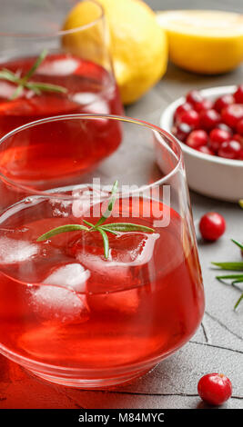 Cold refreshing drink of cranberry, lemon, rosemary and ice cubes. Selective focus - Stock Photo