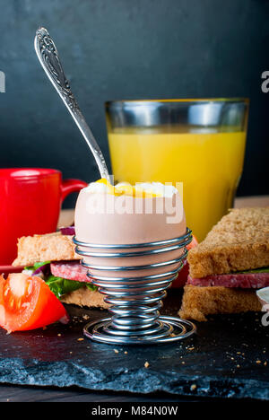 Healthy breakfast with boiled egg in cup, sandwiches, coffee, juice and fruits. Concept healthy eats. Copy space. - Stock Photo