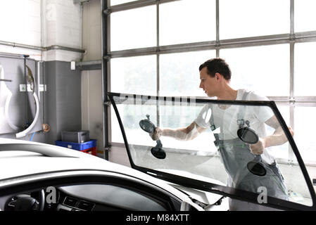 mechanic in a garage replaces defective windshield of a car - Stock Photo