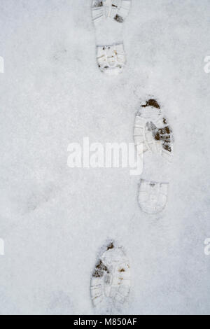 Boot prints on a garden path in the snow. UK - Stock Photo