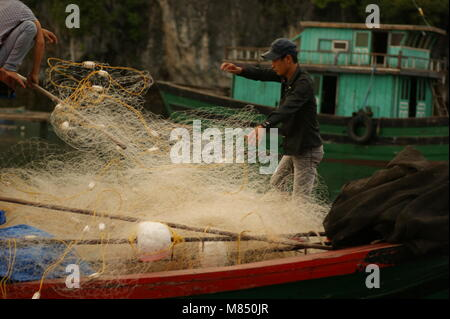 A seafood farm and a peasant settlement in Halong Bay. Fisherman on the boat in the foreground. Vietnam, the South - Stock Photo