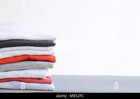 Stack of colorful folded shirts on gray table with empty space for text. Household concept. - Stock Photo