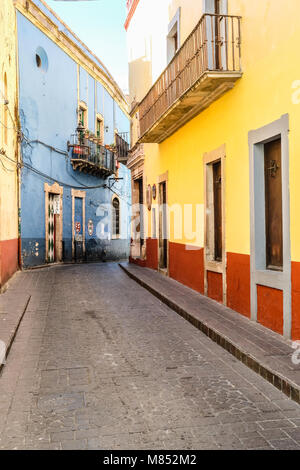 Narrow cobblestone pathway in between colorful houses in Guanajuato, Mexico - Stock Photo