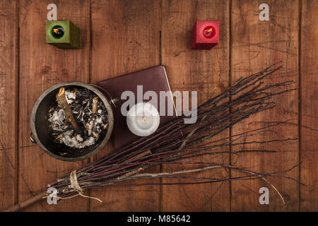 An overhead photo of a witch's cauldron, a grimoire, candles, and a handmade broom. Wiccan ritual objects, shot - Stock Photo