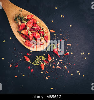Dried Chili peppers mini on a black slate background. - Stock Photo