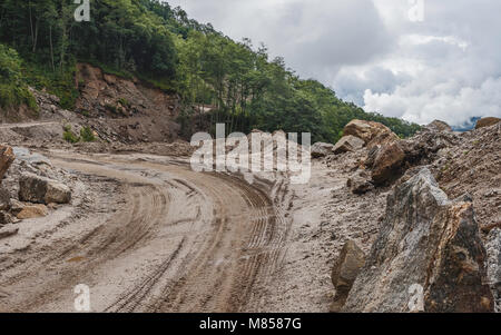 Muddy main highway (H229) between Bomdila and Tawang and forested slopes and thick cloud near Bomdila, Arunachal - Stock Photo