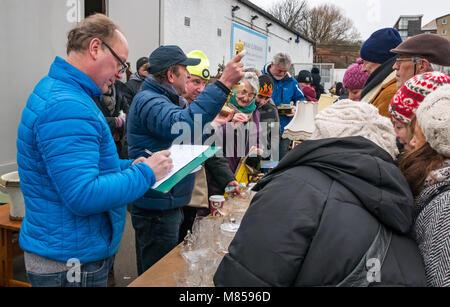 People at lane sale table auction, Ramsey Cornish, Jane Street, Leith, Edinburgh, Scotland, UK, auctioneer holding - Stock Photo