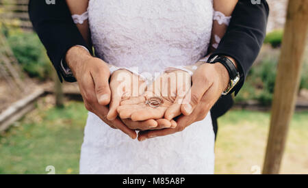 Close up of bride and groom putting their hands together and holding wedding rings on their palms. Close up of two - Stock Photo