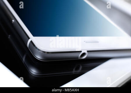 White Business Smartphone With Blue Reflection Lying On White Tablet - Stock Photo