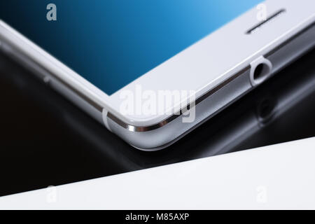 White Business Smartphone With Blue Reflection On White Tablet - Stock Photo