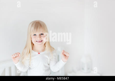 Portrait of little cute girl standing on bed. Adorable smiling child.  Blond kid raising up fists. Children victory - Stock Photo