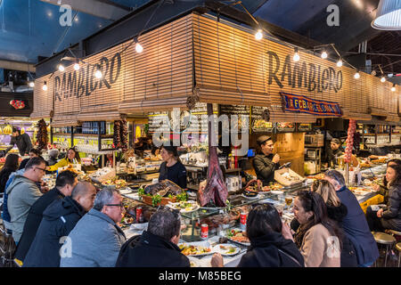 Tourists eating in a tapas bar at Boqueria market, Barcelona, Catalonia, Spain - Stock Photo