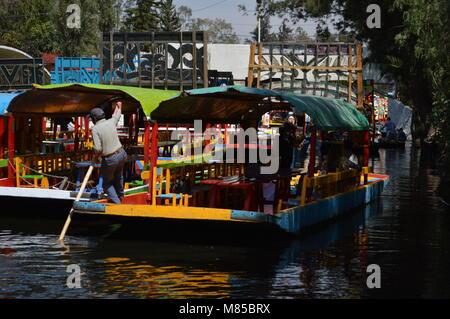 A man steering a trajinera in Xochimilco, Mexico City - Stock Photo