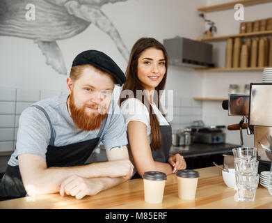 Coffee Business Concept - Positive young bearded man and beautiful attractive lady barista couple in apron looking - Stock Photo