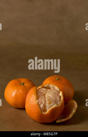 Three clementines, on half-peeled - on brown paper, with copy space - Stock Photo