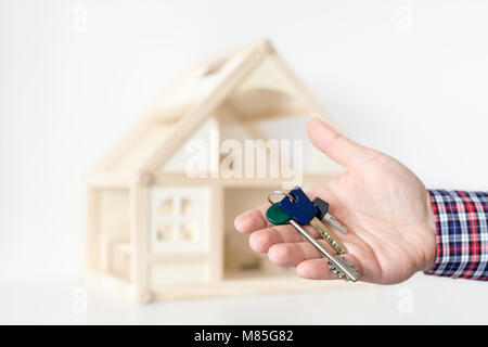 Agent's hand hold keys against house model on background.  Realtor sale offer.  Real estate investment proposition. - Stock Photo