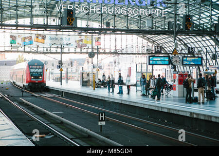 The central station is called Berlin Hauptbahnhof. People are waiting for the train on the platform. The train in - Stock Photo