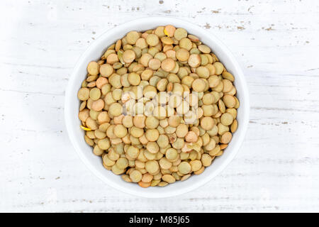 Green lentils raw from above bowl wooden board wood - Stock Photo