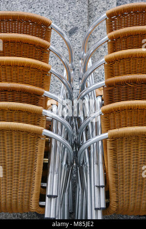 Stacked outdoor metallic and plastic chairs. City background. Vertical - Stock Photo