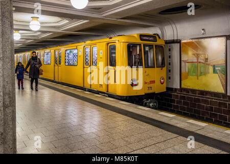 Berlin Dahlem District,Breitenbachplatz U-Bahn underground railway station interior, yellow train and woman with - Stock Photo