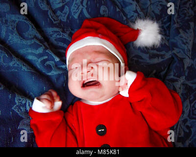 Unhappy Santa  little baby crying on blue background - Stock Photo