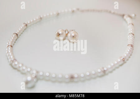 Pearl earrings inside pearl necklace. - Stock Photo