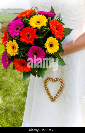 Bouquet of dahlias, wedding flowers and heart decoration held by a bride. - Stock Photo